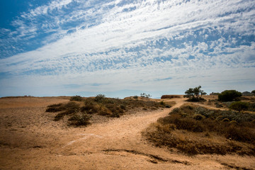 Landscape view with walking trail in Portugal Algarve. Red soil and cloudy sky.