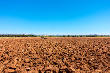 Landscape view of arable land, plowed red soil against blue sky in Algarve Portugal.