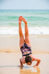 Cute young girl playing on the beach in swimsuit doing a handstand, sea and horizon in the background.