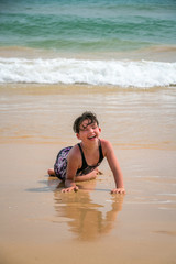 Cute young little girl laughing laying in a swimsuit in the sand on a beach with waves.
