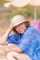 Beautiful summer portrait of middle aged woman in sun hat and glasses on the beach.