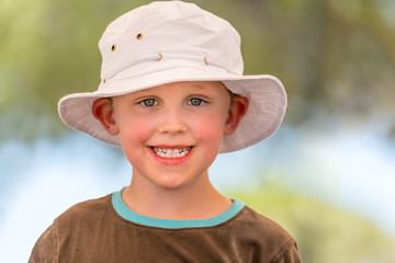 Outdoor summer portrait of cute smiling boy in white hat. Selective focus with shallow depth of field.