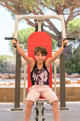 Cute young girl exercising upper body on gym machine outdoors in Portugal surrounded by nature.