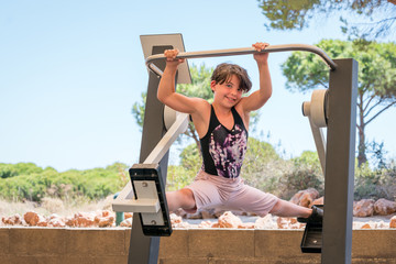 Cute young girl exercising, doing the splits on cross trainer gym machine outdoors in Portugal surrounded by nature.