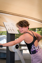 Cute young girl exercising upper body on gym training machine outdoors in Portugal surrounded by nature.