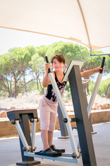 Cute young girl exercising arms and chest on cross trainer gym machine outdoors in Portugal surrounded by nature.