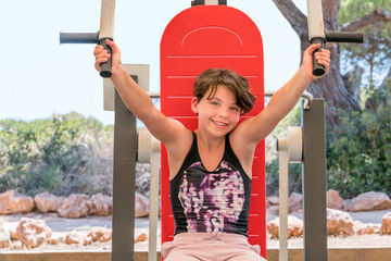 Cute young girl exercising arms and chest on gym machine outdoors in Portugal surrounded by nature.