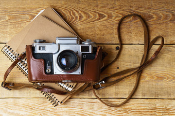 Old retro camera,  spiral blank kraft paper notebook on vintage rustic wooden planks boards. Education photography courses back to  school concept abstract background. Close up, horizontal, top view.
