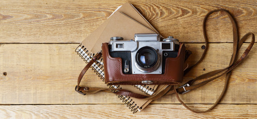 Old retro camera, spiral blank kraft paper notebook on vintage rustic wooden planks boards. Education photography courses back to  school concept abstract background. Close up, top view, copy space.