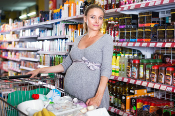Girl is showing chosen purchases from trolley in supermarket.