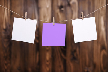 Close up of two white and one violet note papers hung by wooden clothes pegs on a brown wooden background