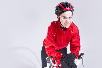 Cycling Ideas And Concepts. Portrait of Caucasian Female Cyclist Equipped in Cycling Outfit and Posing With Road Bike In Studio.