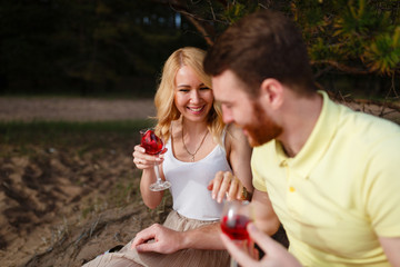 Young man and girl sitting and hugging in the woods and drink wine. Young beautiful couple smiling and drinking wine on picnic in summer Park on green grass near forest