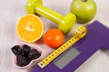 Digital scale, centimeter, dumbbells and fruits, healthy nutrition and slimming concept