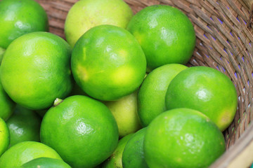 group of Fresh organic green lime Citrus lemon in wooden tray, at fresh market on asian fruit section