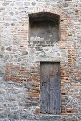 Ancient wooden door on a brick wall