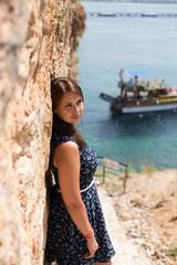 Woman with straight brown hair wearing dark blue dress