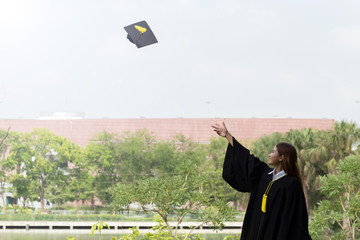 Graduate throwing graduation cap to the sky and holding certificated in her hand