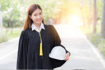 Asian woman graduate in gown smile with engineer white helmet