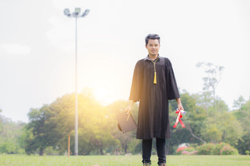 Happy Graduate man in gown standing and holding cap and certificated