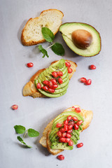 sliced avocado on toast bread with pomegranate seeds.