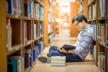 Young Asian man university student reading book in library, education research and self learning in university life concepts