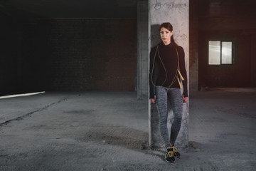 Young woman in sportswear standing near concrete column with jump-rope