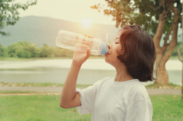 girl drinking water after exercise in park