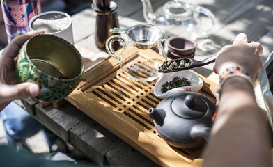Traditional Chinese tea ceremony - a hand holding a wooden spoon with Chinese green tea