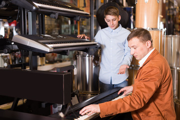 Young boy and father deciding on synthesizer