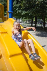 Little girl on the playground in summer
