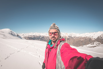 Adult alpin skier with beard, sunglasses and hat, taking selfie on snowy slope in the beautiful italian Alps with clear blue sky. Concept of wanderlust and adventures on the mountain. fisheye lens.