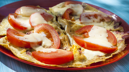 Scrambled eggs with tomatoes and cheese on a sunny morning