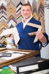 attentive man seller in picture framing studio with wooden details