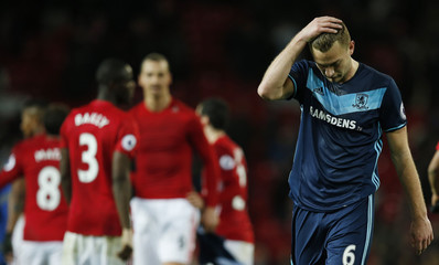 Middlesbrough's Ben Gibson looks dejected as Manchester United players celebrate after the game