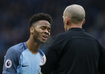 Manchester City's Raheem Sterling reacts after being shown a yellow card by referee Mike Dean for simulation