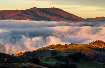 rising clouds in mountainous countryside at sunrise