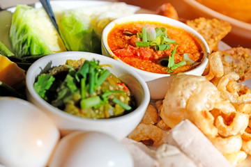 Thai food - Northern style red and green chilli dips with  northern thai spicy sausage (sai oua), streaky pork with crispy crackling and  vegetables