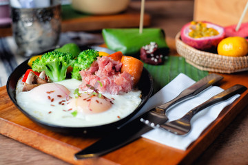 Breakfast - Fried eggs with sausages, fermented pork and vegetable served with fruits