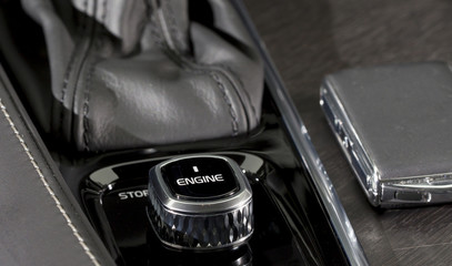 Engine start and stop button in a modern and luxury car. Black interior, expensive model.
