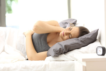 Woman suffering neck ache in an uncomfortable bed