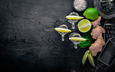 Tequila with lime, lemon, and salt on a black background Wooden. Free space for text . Top view.