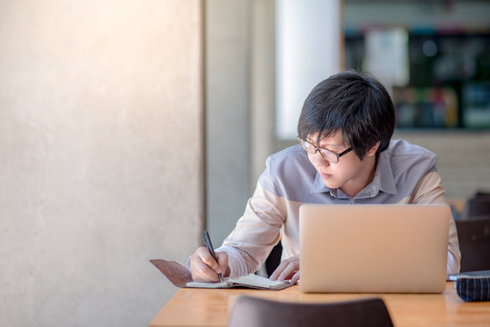 Young Asian man writing on notebook and working with laptop computer in college building. high school or university student, educational concepts