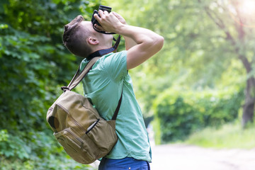A young man takes photos of nature in the woods