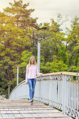 Blonde funny happy pretty girl in a pink sweatshirt on the bridge in park. Sunny day.