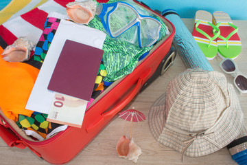 Suitcase with things for spending summer vacation things prepared for travel. suitcase with clothing on table