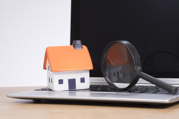 Miniature of house with magnifying glass on laptop
