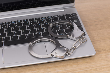 Open laptop with locked handcuffs on the keyboard