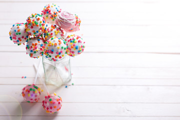 Colorful bright cake pops  in  jar on  white wooden   background.