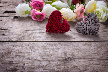 Two decorative  hearts  and flowers on vintage wooden background.
